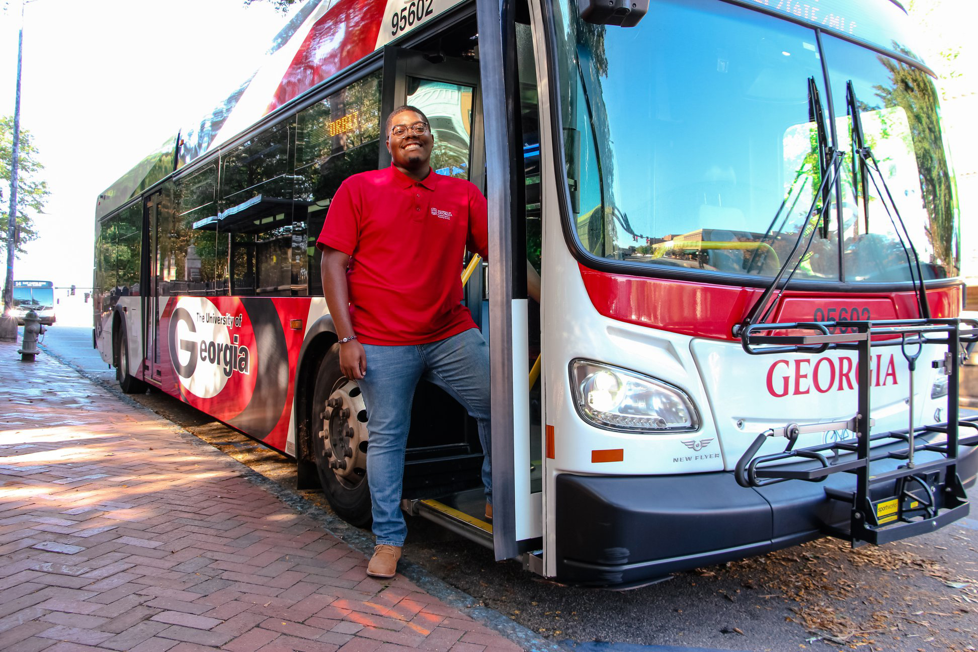 A bus driver stands next to a UGA bus.