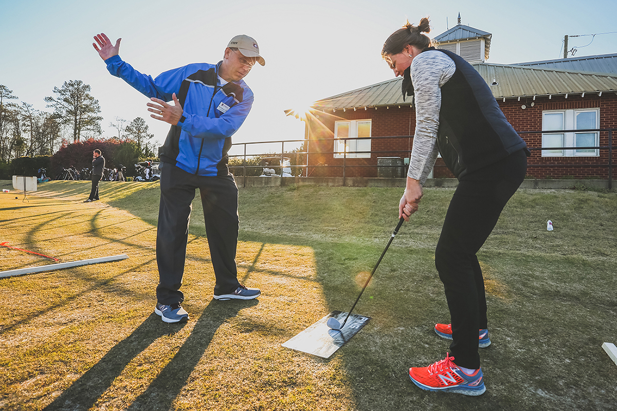 A golfer gets instruction on her swing.